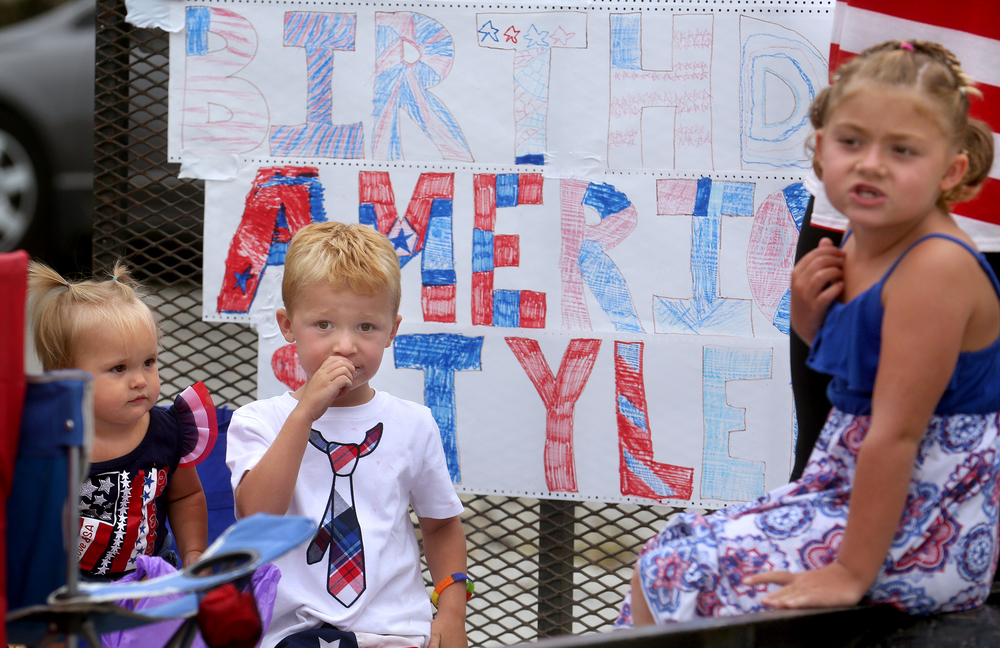 The Smith children of Loami left to right: Hallie, 1, Tyler, 5, and Peyton, 6, wore their patriotic best as they prepare to ride in a family float adorned with a hand-drawn tribute to America's birthday on Saturday. David Spencer/The State Journal-Register