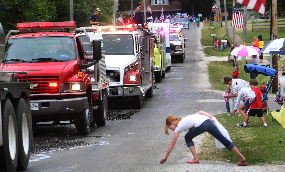 Emergency vehicles from Loami and the surrounding area made up the front part of the parade, seen here making their way on Church St. during the parade as a child gathers candy in foreground on Saturday. David Spencer/The State Journal-Register