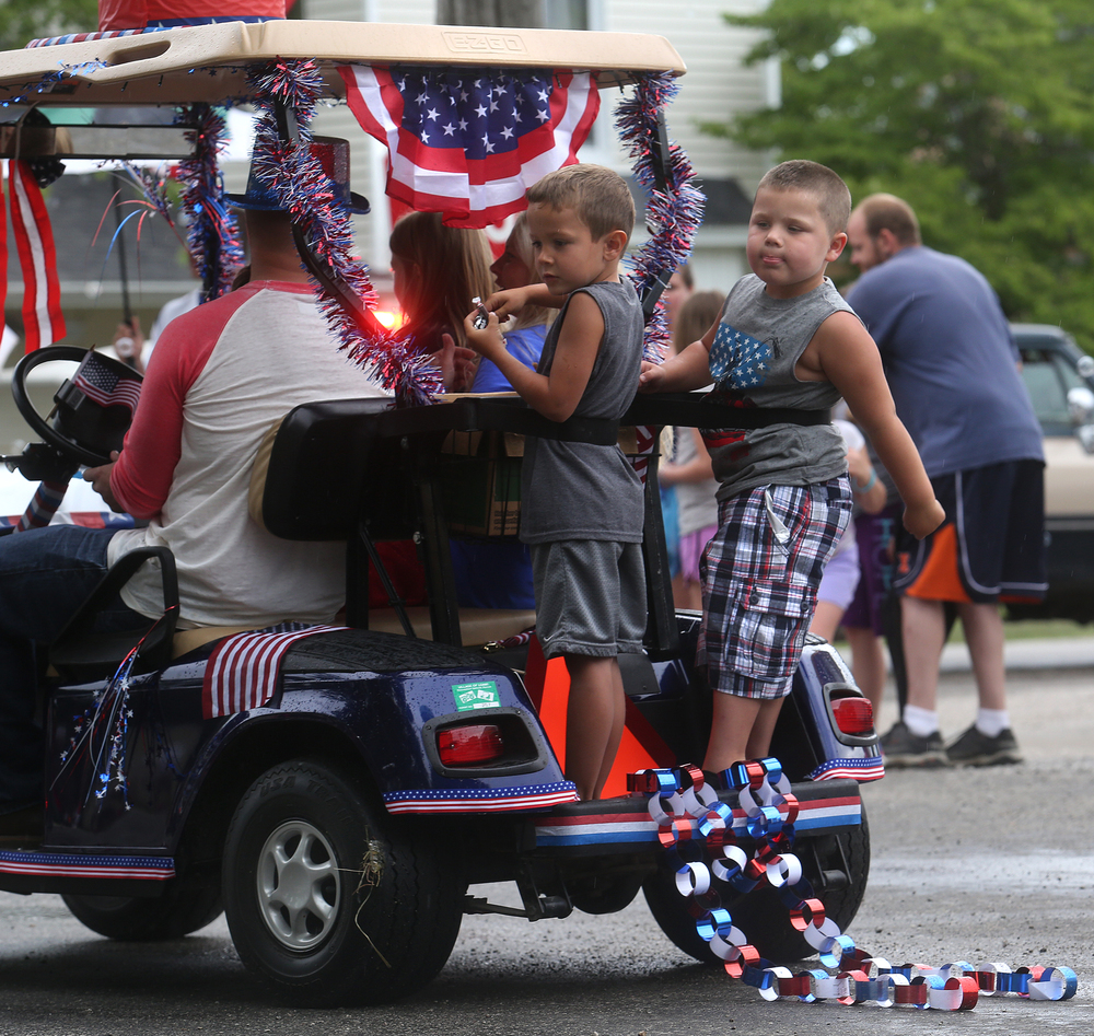 Children riding on the rear of a patriotically embellished golf cart are strapped in as they prepare to toss candy to those lining the village square on Saturday during the parade. David Spencer/The State Journal-Register