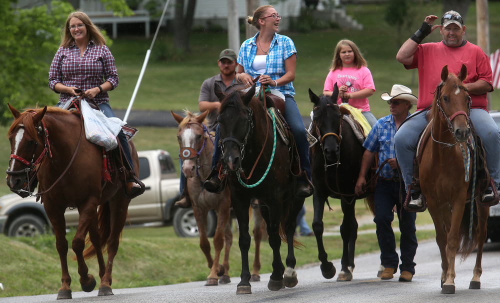 Horses stabled at Petersburg's Double V Ranch make their way with riders aboard down S. Main Street during the parade Saturday morning. David Spencer/The State Journal-Register