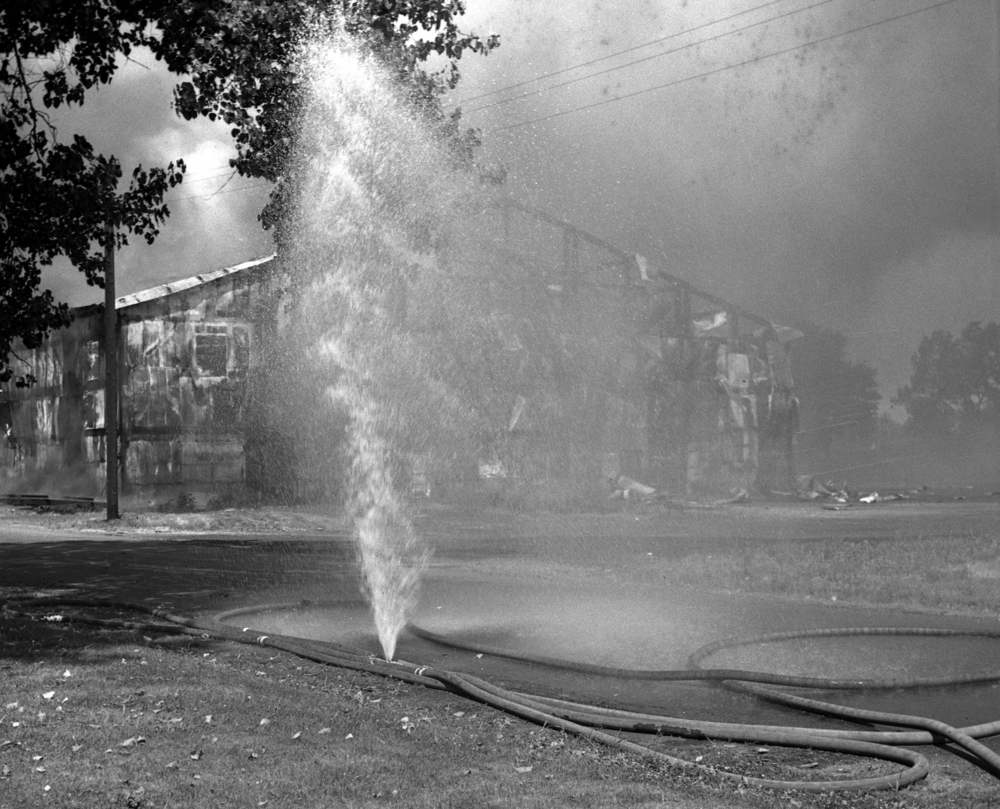 A hose began leaking while Springfield fire fighters battled a fire at the Ridgely Avenue sale barn, 1301 Ridgely Ave. July 30, 1947. File/The State Journal-Register