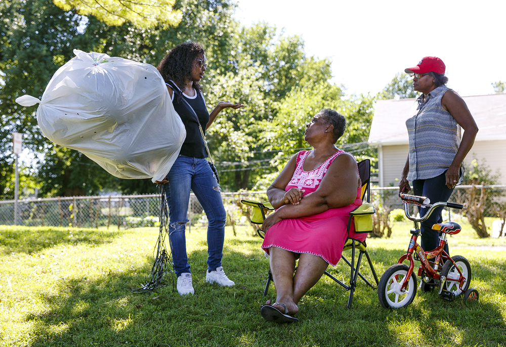 Twyla Lewis, left, visits with Mary Adams, center, and Frankie Brooks at Comer Cox Park before marching to the Illinois capitol building to remember the victims of the police shootings and the Dallas officers killed Thursday night.  Ted Schurter/The State Journal-Register