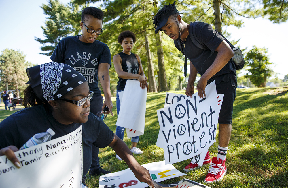 Jaylin Netters gathers signs at Comer Cox Park before a march to the Illinois capitol building to remember the victims of the police shootings and the Dallas officers killed Thursday night. Ted Schurter/The State Journal-Register