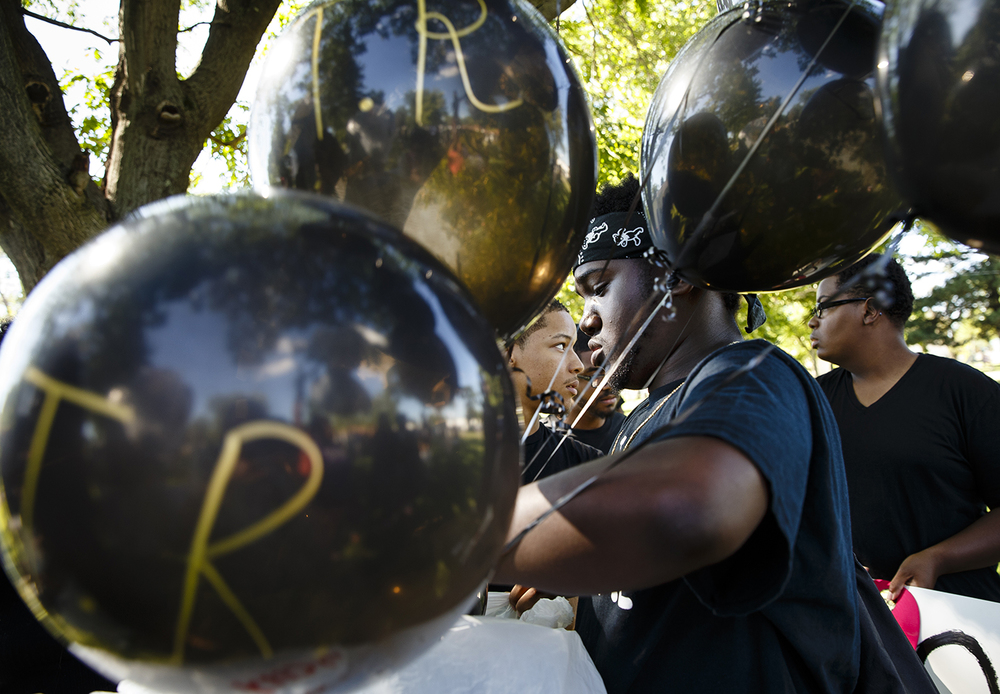 Fletcher Williams Jr. holds black balloons as participants sign the initials of each black person killed by police, 123 total in 2016, before they were released at the conclusion of a march to the Illinois capitol building Friday, July 8, 2016. Ted Schurter/The State Journal-Register
