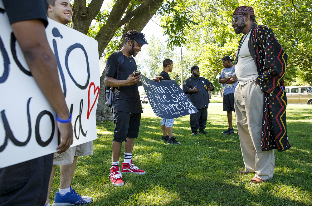Jaylin Netters, left,  one of the event organizers, visits with Aaron Pinkston-El before a march to the Illinois capitol building to remember the victims of the police shootings and the Dallas officers killed Thursday night. Ted Schurter/The State Journal-Register