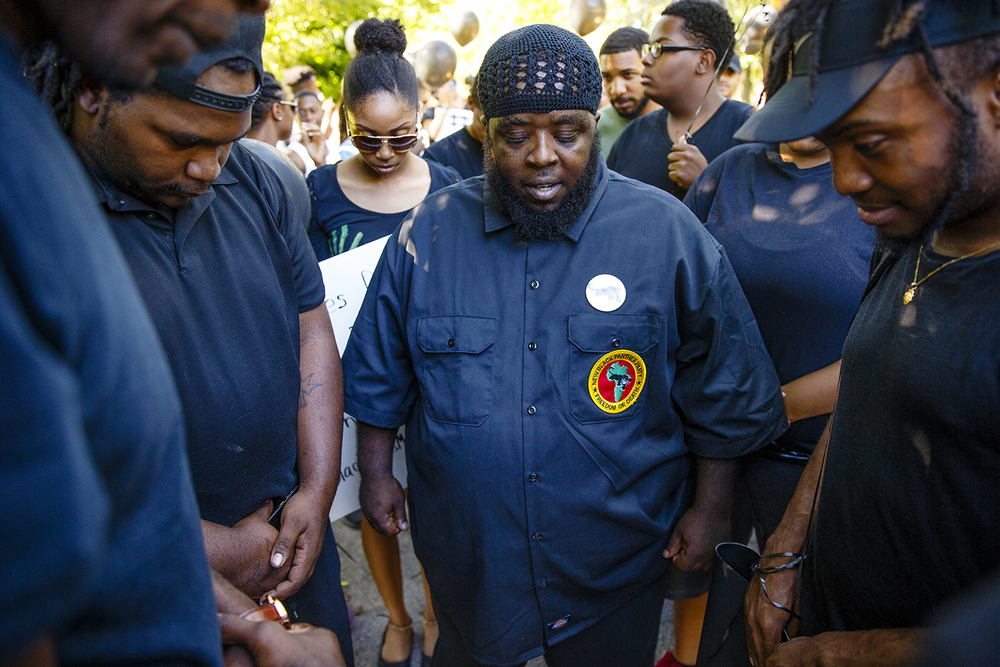 Keith Muhammad with the New Black Panther Party in Springfield says a prayer before the a march to remember the victims of violence, including police shootings and the Dallas officers killed Thursday night, steps onto Capitol Avenue and heads to the capitol building Friday, July 8, 2016. Ted Schurter/The State Journal-Register