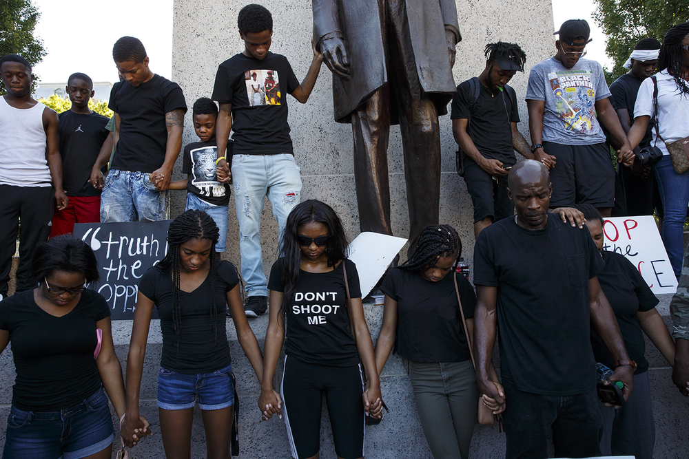 Protesters gather in prayer under the statue of Abraham Lincoln at the conclusion of a march to remember the victims of violence, including police shootings and the Dallas officers killed Thursday night, Friday, July 8, 2016. Ted Schurter/The State Journal-Register