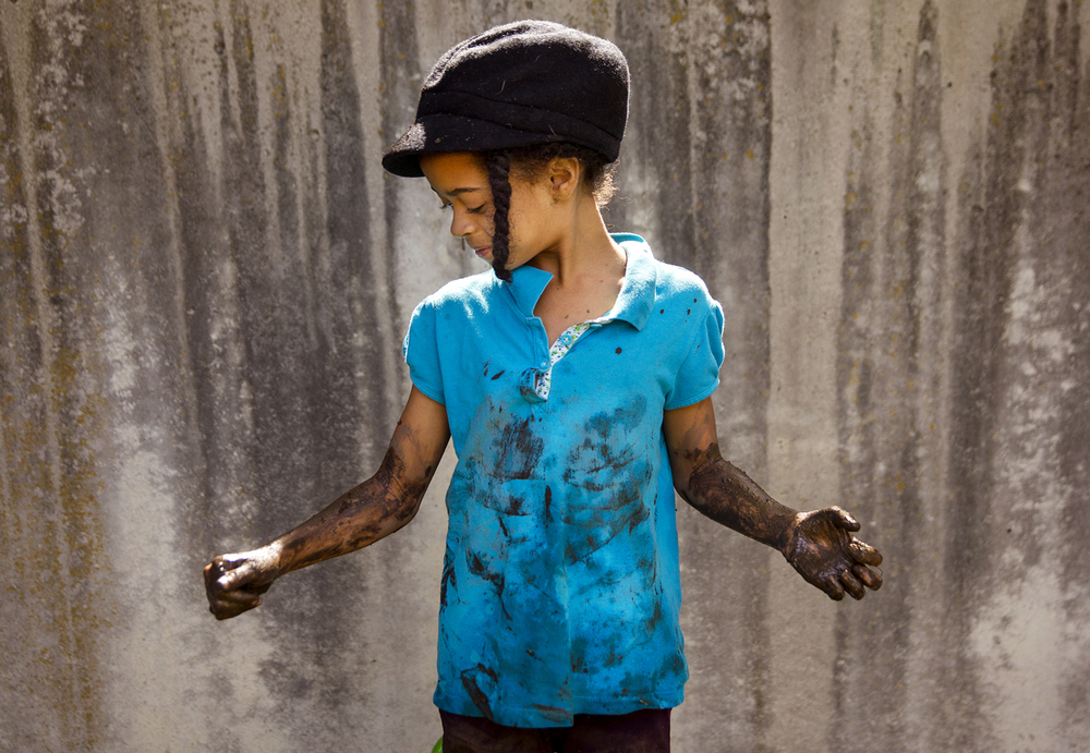 Te'Asia Durbin glances at the mud coating her arms after climbing out of a mud hole at Adventurous Learning daycare in Springfield during International Mud Day Wednesday, June 29, 2016. Ted Schurter/The State Journal-Register
