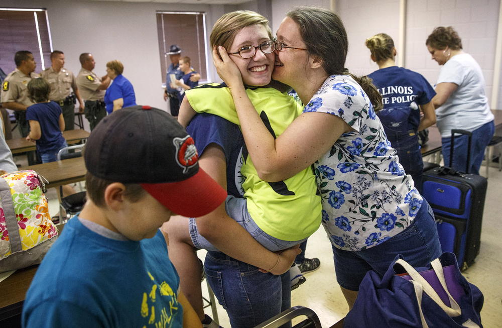 Miranda Smith gets a kiss from her mom Juli as her brother Joshua wraps her up in a hug after she graduated from the 44th Annual American Legion Youth Police Camp at the Illinois State Police Academy Friday, July 1, 2016. The week-long residency camp is structured to promote educational and learning opportunities for kids ages 14 to 16 in the areas of law enforcement, military, leadership, cultural diversity, personal development, physical fitness, and social and interpersonal skills. Ted Schurter/The State Journal-Register