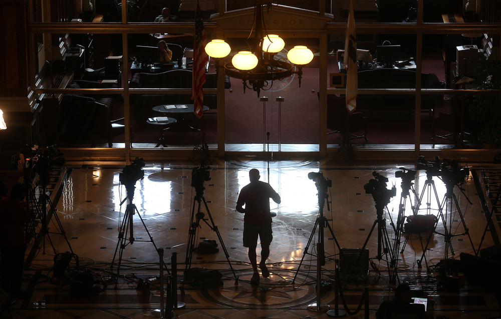 A member of the media is silhouetted along with television cameras positioned outside the Governor's office at the Illinois Statehouse in Springfield on Wednesday afternoon, June 29, 2016.  Illinois legislative leaders continued to meet on Wednesday on an agreement for a stopgap state budget bill and funding for K-12 education. David Spencer/The State Journal-Register