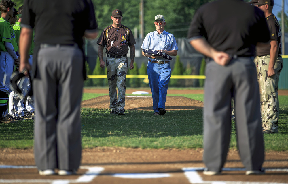 "U.S. Military All-Stars head coach Bodacious Ball, left, performs the ""Walk of Honor"" with Shelby Fuller, an Air Force veteran and retired Illinois Air National Guard, prior to an exhibition game with the U.S. Military All-Stars and the Springfield Sliders at Robin Roberts Stadium, Tuesday, July 5, 2016, in Springfield, Ill. Fuller was honored by throwing out the first pitch on his 74th birthday. The U.S. Military All-Stars have players from all military branches and was founded in 1990 after  President George H.W. Bush discussed the positive impact baseball had on morale during World War II during a visit to the National Aviation Museum. Justin L. Fowler/The State Journal-Register"