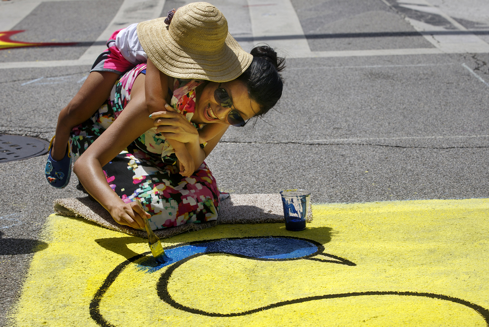 Avaani Basnet rides on Asmita Dhukhwa's back as she creates a painting during the Springfield Art Association's Paint the Street event in downtown Springfield Saturday, July 9, 2016. Ted Schurter/The State Journal-Register