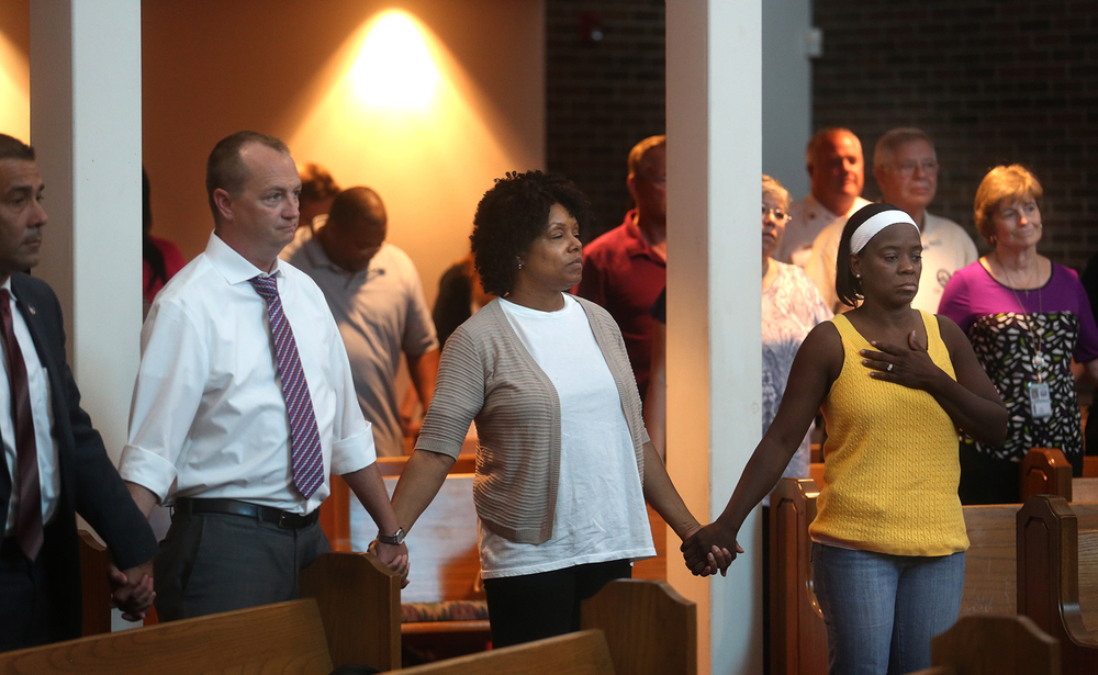 Those attending the prayer service clasp hands with each other in the sanctuary at Pleasant Grove. About 50 people gathered at Pleasant Grove Baptist Church in Springfield on Friday afternoon, July 8, 2016 to pray for this week's victims of police shootings and the Dallas police officers who were shot Thursday night. David Spencer/The State Journal-Register