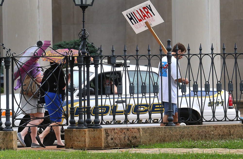 A gentleman with a sign alluding to his belief Hillary Clinton lied after the 2012 Benghazi attack walked the outer perimeter of the Old State Capitol plaza along Sixth St. Wednesday morning. David Spencer/The State Journal-Register