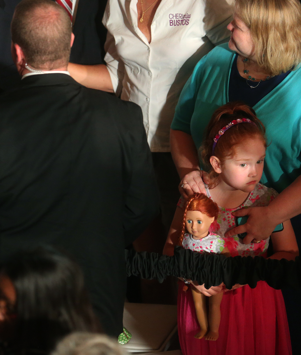 A young supporter who had shook Hillary Clinton's hand earlier waits along with her doll as a secret service agent at left escorts Clinton off the floor of Representatives Hall early Wednesday afternoon. David Spencer/The State Journal-Register