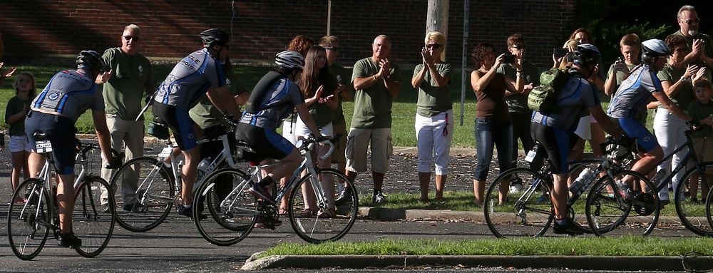 COPS bicyclists get back on the road again as David Tapscott family members clap in background at the conclusion of the ceremony honoring his memory Friday morning. David Spencer/The State Journal-Register