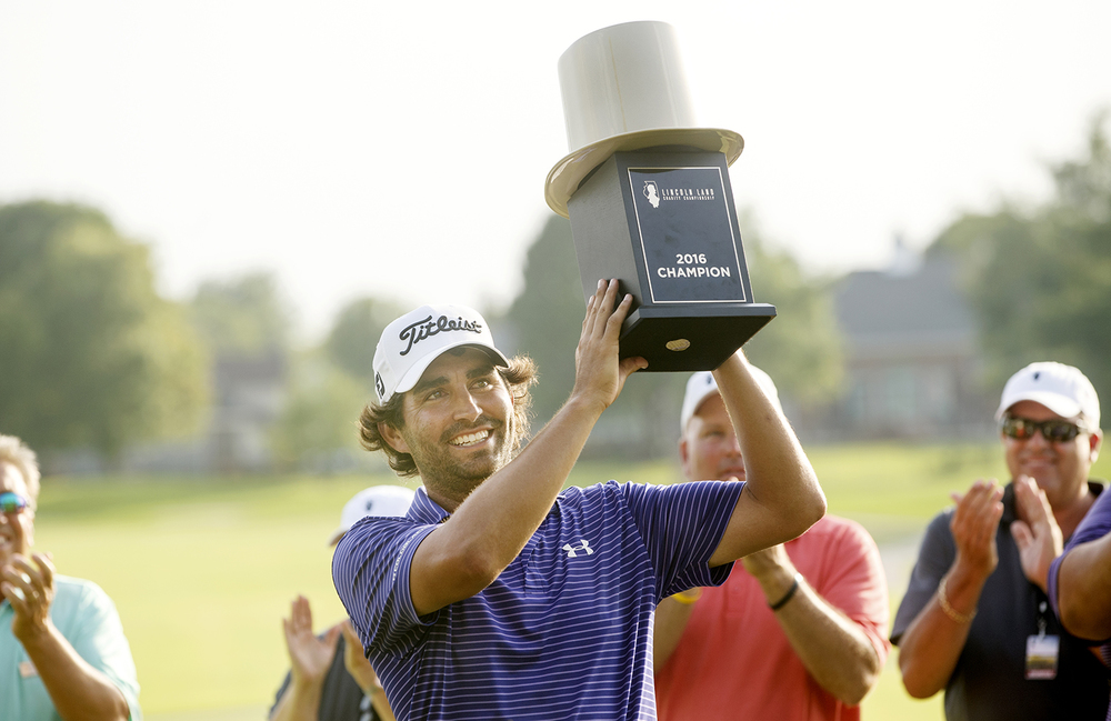 Martin Flores hoists his new trophy after getting the first victory of his career during the the inaugural Web.com Tour Lincoln Land Charity Championship at Panther Creek Country Club Sunday, July 17, 2016. Ted Schurter/The State Journal-Register