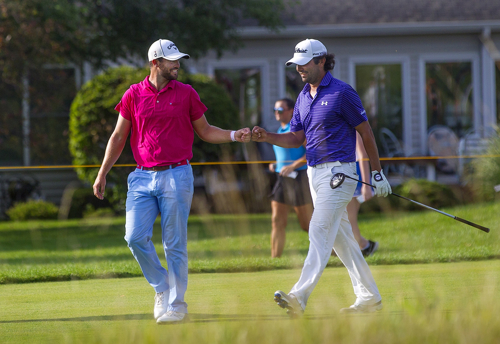 Wesley Bryan, left, gives Martin Flores a fist bump as they walk the fairway on the 17th hole during the the inaugural Web.com Tour Lincoln Land Charity Championship at Panther Creek Country Club Sunday, July 17, 2016. Flores won the event and Bryan tied for 2nd with four other golfers. Ted Schurter/The State Journal-Register