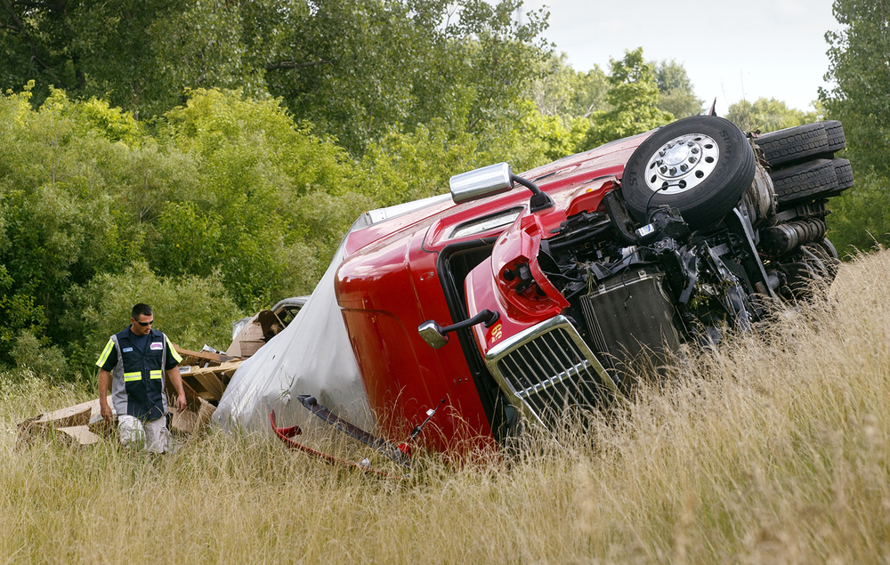 A Shaner's Towing employee inspects the scene where a tractor trailer rolled down an embankment off Interstate 55 near Glenarm Monday, July 18, 2016.  Ted Schurter/The State Journal-Register