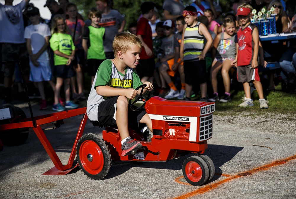 Connor Rich, 6, builds up his power as he tries to go the distance in the six-year-old division of the Pedal Tractor Pull during the Morrisonville Homecoming and Picnic, Wednesday, July 20, 2016, in Morrisonville, Ill. The event continues on Thursday with the parade and the annual frog jumping contest. Justin L. Fowler/The State Journal-Register