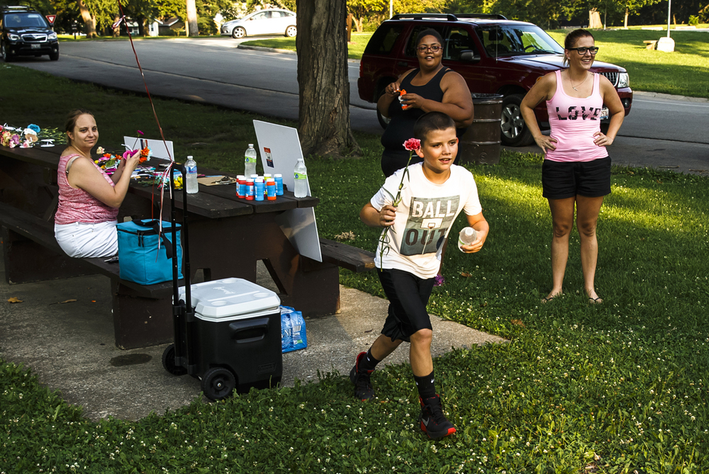 "Michael Rodriguez 12, sprints away towards a couple walking in Lincoln Park to offer them a flower and a bottle of water along with his mother Dana Goodrum, center, and her friends, Barbara Wheatley and Dawn Holloway, left, Thursday, July 21, 2016, in Springfield, Ill. Goodrum set out to show her children a way to spread love and kindness with just a simple act of giving away flowers with the message ""All You Need is Love.""  Justin L. Fowler/The State Journal-Register"