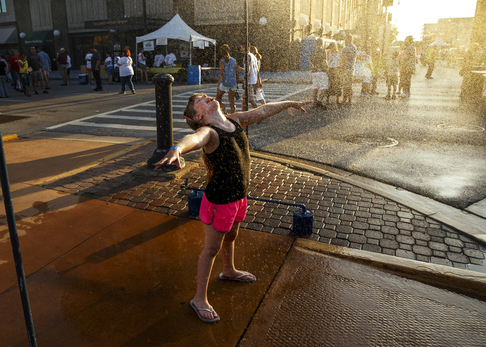 Natalie Spann sticks out her tongue as she stands under a mister during the Downtown Bacon Throwdown Friday, July 22, 2016. Patrons battled triple digit heat indexes until after sunset when the temperature began to fall. Ted Schurter/The State Journal-Register