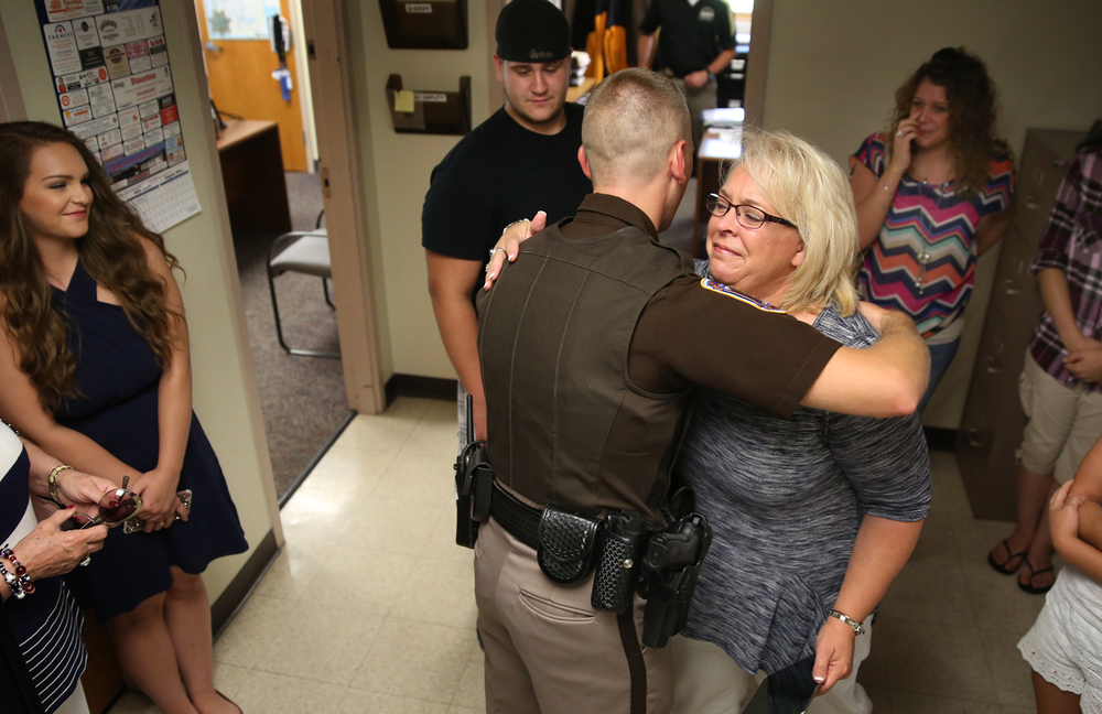 Dawn Montgomery of New Berlin, the mother of Alex Cardwell, embraces deputy Larry Rayburn during the ceremony Thursday morning as family members look on including Cardwell in background. Macoupin County Sheriff's deputy Larry Rayburn was honored in a ceremony at the Sheriff's office in Carlinville on Thursday, July 21, 2016 for saving the life of New Berlin resident Alex Cardwell. Cardwell suffered a severe asthma attack while camping at Otter Lake near Girard on May 26 of this year.  David Spencer/The State Journal-Register