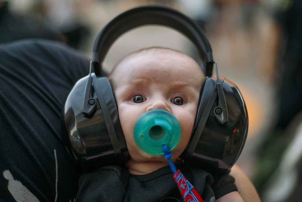 Three-month-old Logan Russell wears an industrial sized set of ear protection as he rests in his dad Patrick's arms after watching him perform at the Downhome Music Festival in downtown Springfield Friday, July 29, 2016. Ted Schurter/The State Journal-Register