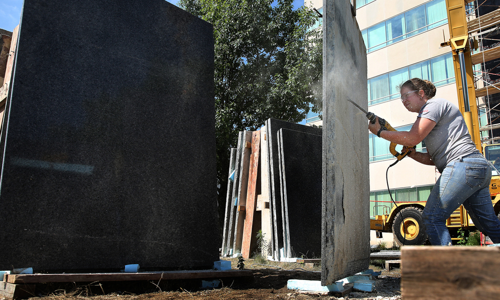 Surrounded by granite panels removed from Municipal Center East at left, Evans-Mason employee Meaghan Mason strips old mortar from one of the panels that will soon be hoisted by crane and re-attached to the face of the building seen behind her on Tuesday, July 26, 2016. Improvements and beautification are now ongoing projects at Municipal Center East, for both the building and the grounds in Springfield. Evans-Mason Inc. has begun the process of reattaching over 50 granite panels to the east face of the building after first removing them with a crane and replacing their anchors in addition to waterproofing the face of the building. On the grounds, Central Stone & Landscape Supply is creating new mulched border gardens featuring weathered limestone fieldstone boulders from Arkansas and planting new flowers along with re-purposed plantings. David Spencer/The State Journal-Register