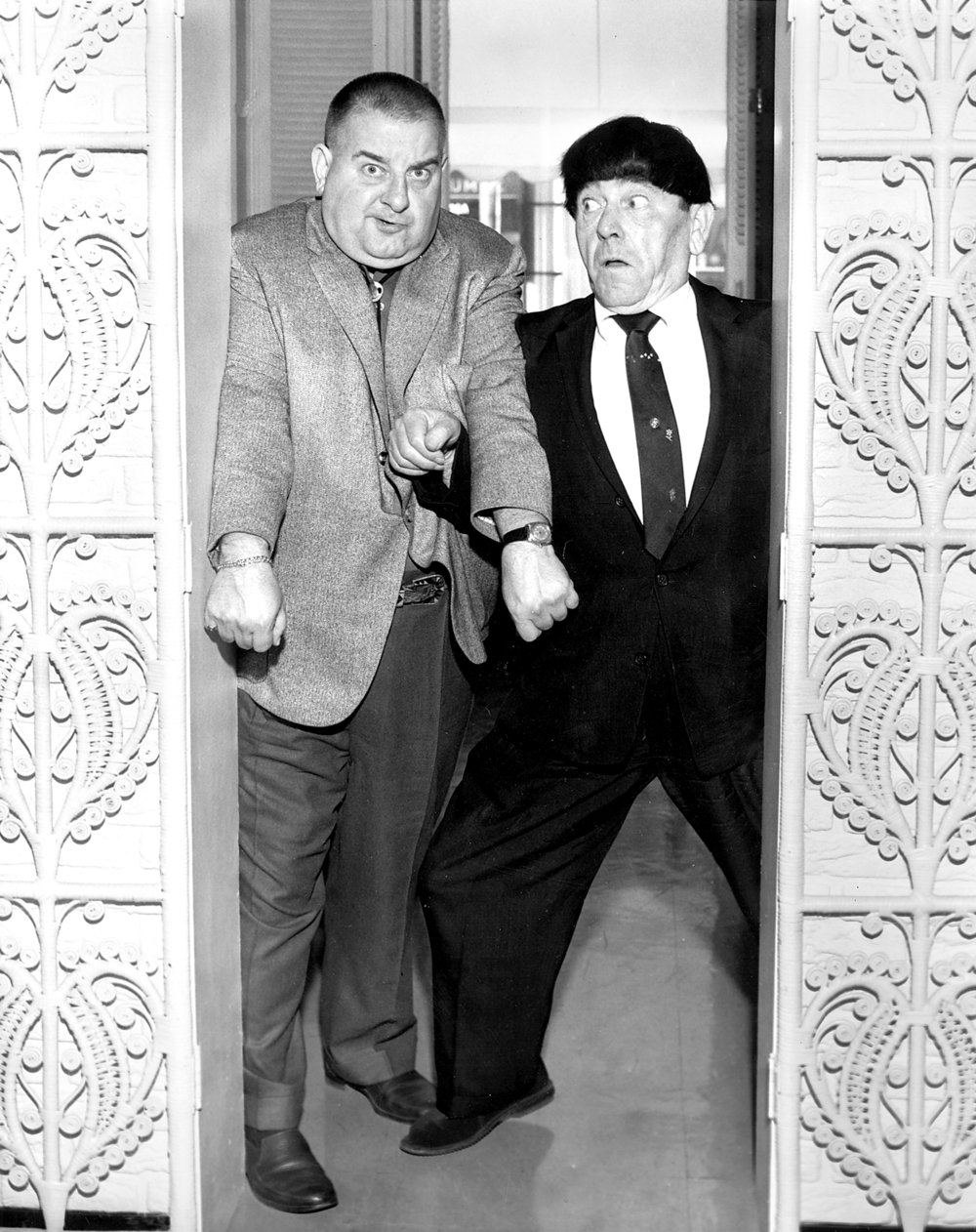 "Two of the Three Stooges arrived a day early for the 1960 Illinois State Fair.  ""Curley"", Joe DeRita, left, and Moe Howard, right,  clown around in the Leland Hotel lobby for a photo.  The third ""Stooge"", Larry Fine, came in the next day."