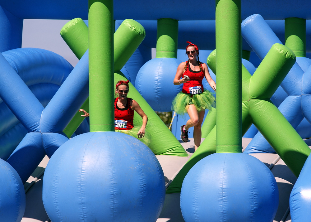 Amber Rector, left, and her cousin, Emily Briney, negotiate their way through one of the obstacles during the Insane Inflatable 5k fun run at Centennial Park Saturday, Aug. 6, 2016. Rich Saal/The State Journal-Register