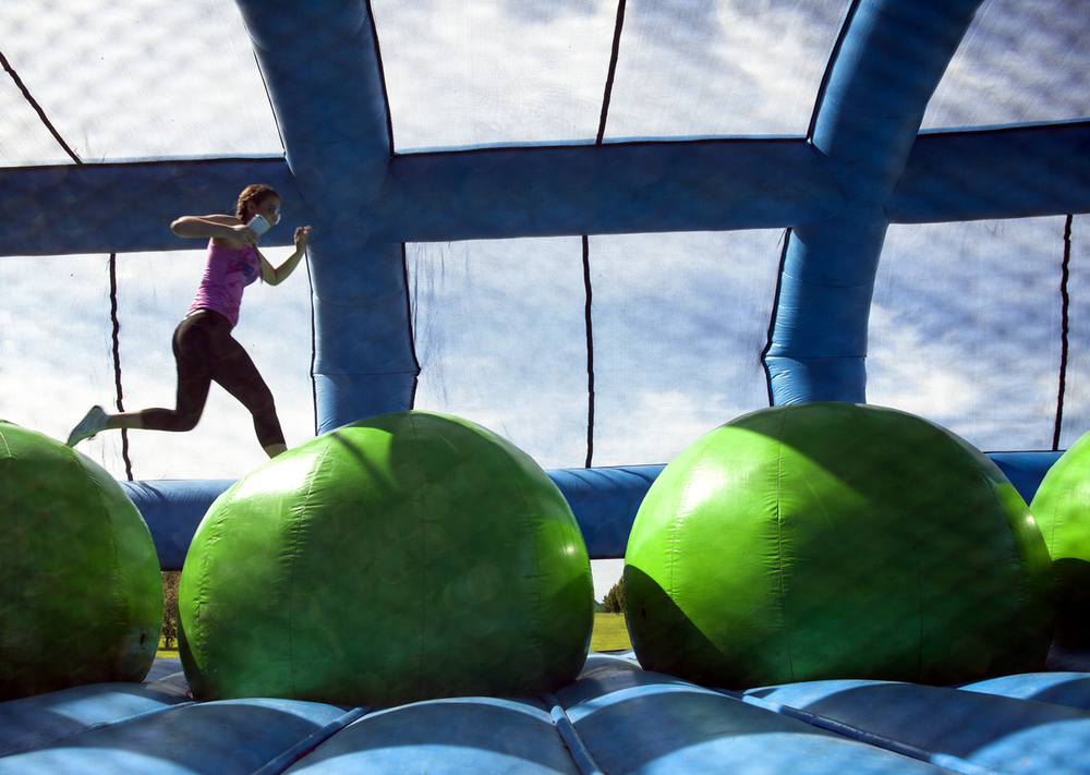 A participant jumps from one ball to another inside one of the obstacles at the Insane Inflatable 5k fun run at Centennial Park Saturday, Aug. 6, 2016. Rich Saal/The State Journal-Register