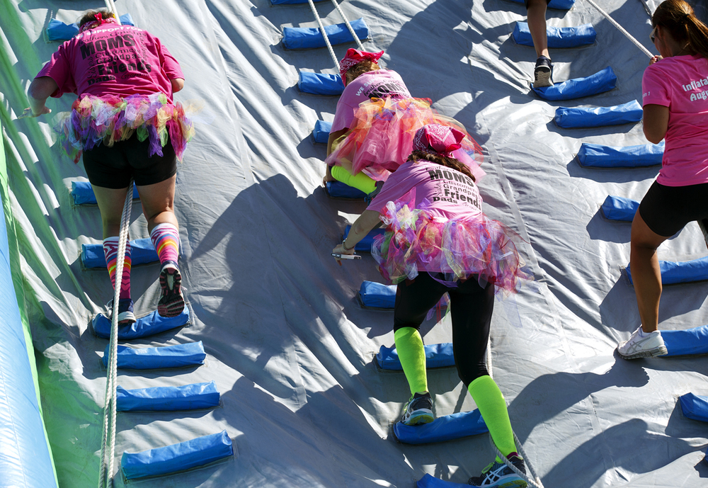 A team in matching outfits climbs the final obstacle on the course at the Insane Inflatable 5k fun run at Centennial Park Saturday, Aug. 6, 2016. Rich Saal/The State Journal-Register