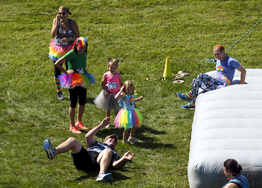 A participant tumbles off the landing pad of an obstacle in the Insane Inflatable 5k fun run at Centennial Park Saturday, Aug. 6, 2016. Rich Saal/The State Journal-Register