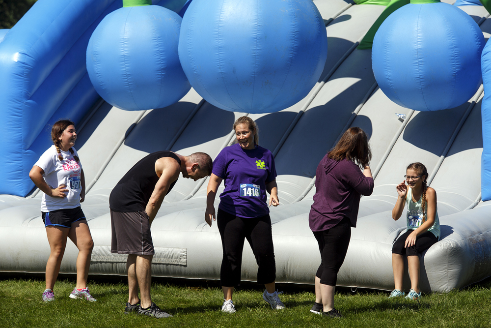 Sydnee Guzouskis, left, and her dad Jim, and Sara Weurtzler and her daughters, Isabelle and Grace, catch their breath after completing one of the obstacles during the Insane Inflatable 5k fun run at Centennial Park Saturday, Aug. 6, 2016. Rich Saal/The State Journal-Register