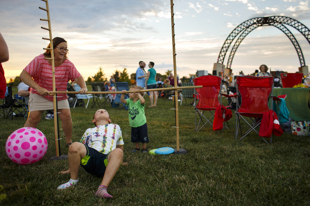 Charlie Davis limbos under the bar as Lynn Saputo and Lincoln Proctor hold the bar in place during the Springfield Municipal concert under the Selvaggio Arches at Southwind Park Sunday, July 31, 2016. Ted Schurter/The State Journal-Register