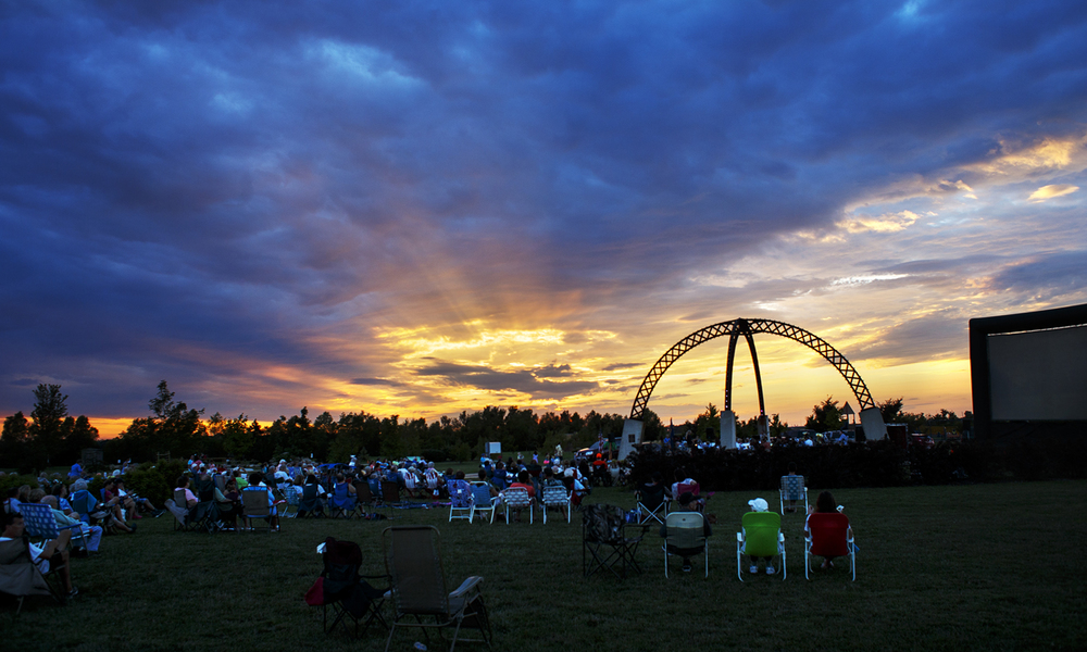 The sun sets behind the Springfield Municipal band as they perform under the Selvaggio Arches at Southwind Park Sunday, July 31, 2016. Ted Schurter/The State Journal-Register
