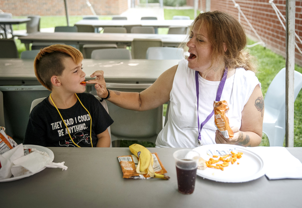 Amanda Taylor, right, serves up Cheetos to her 7-year-old son, Wesley, as they spend their lunch together during the Mom and Me camp at the Logan Correctional Center, Tuesday, Aug. 2, 2016, in Lincoln, Ill. Participants in the three day camp get to spend eight hours with their mothers during the day at the prison and then go back to a campground in Bloomington for the nights where they get to forge bonds with other children in the same situation. Justin L. Fowler/The State Journal-Register