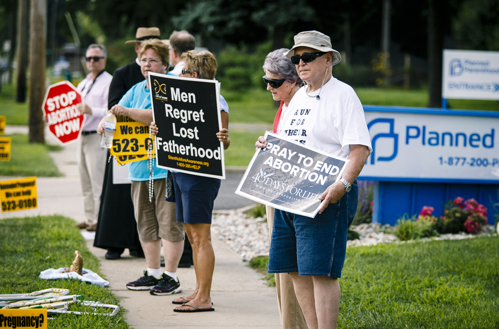 Merle King, and his wife, Betty, stood along with protesters in front the Planned Parenthood facility for a Springfield Right to Life protest against the recent announcement that the local clinic will offer surgical abortions, Thursday, Aug. 4, 2016, in Springfield, Ill. Justin L. Fowler/The State Journal-Register