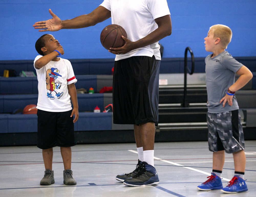 Isaiah Perry, left, and Peyton Campbell listen to the instructions from Femi Akinpetide, director of the Nike-sponsored Pro Level Training basketball camp Tuesday, Aug. 2, 2016 at the Boys and Girls Club of Central Illinois. The week-long camp for boys and girls age 7-14 emphasizes basketball fundamentals, as well as reinforcing positive off-court activities and proper nutrition. Akinpetide is a former college and semi-pro basketball player. Rich Saal/The State Journal-Register