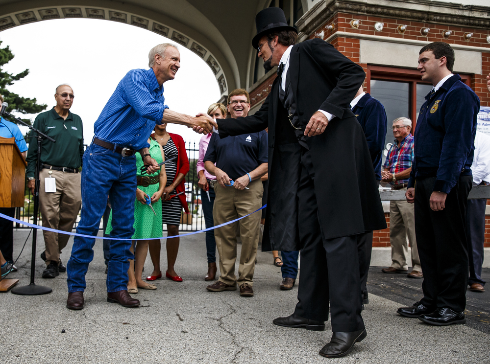 Illinois Gov. Bruce Rauner gets a greeting from Abraham Lincoln, presented by George Buss, as he arrives for the ribbon cutting to open the 2016 Illinois State Fair at the Main Gate of fairgrounds, Friday, Aug. 12, 2016, in Springfield, Ill. Justin L. Fowler/The State Journal-Register