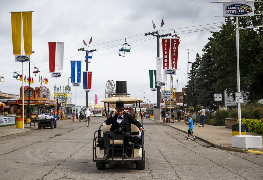Abraham Lincoln, presented by George Buss, hitches a ride on the Looking for Lincoln golf cart with a familiar hat attached to the top during the 2016 Illinois State Fair at the  Illinois State Fairgrounds, Friday, Aug. 12, 2016, in Springfield, Ill. Justin L. Fowler/The State Journal-Register