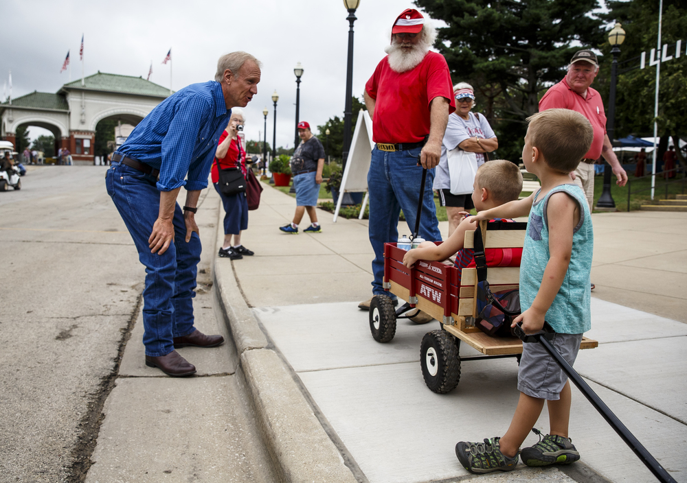 Illinois Gov. Bruce Rauner, visits with Rick Jones, and his grandson Garret Bauer, of Nokomis, Ill., as he makes his way down Main Street after opening the 2016 Illinois State Fair at the Illinois State Fairgrounds, Friday, Aug. 12, 2016, in Springfield, Ill. Justin L. Fowler/The State Journal-Register