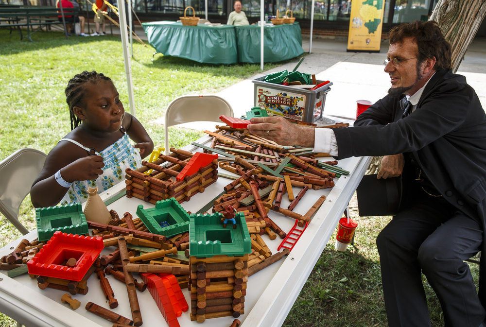 Chloe Davis, 7, works on building a house with a set of Lincoln Logs with the help of Abraham Lincoln, presented by George Buss, at the Looking For Lincoln exhibit on the lawn of the Illinois Building during the 2016 Illinois State Fair at the Illinois State Fairgrounds, Friday, Aug. 12, 2016, in Springfield, Ill. Justin L. Fowler/The State Journal-Register