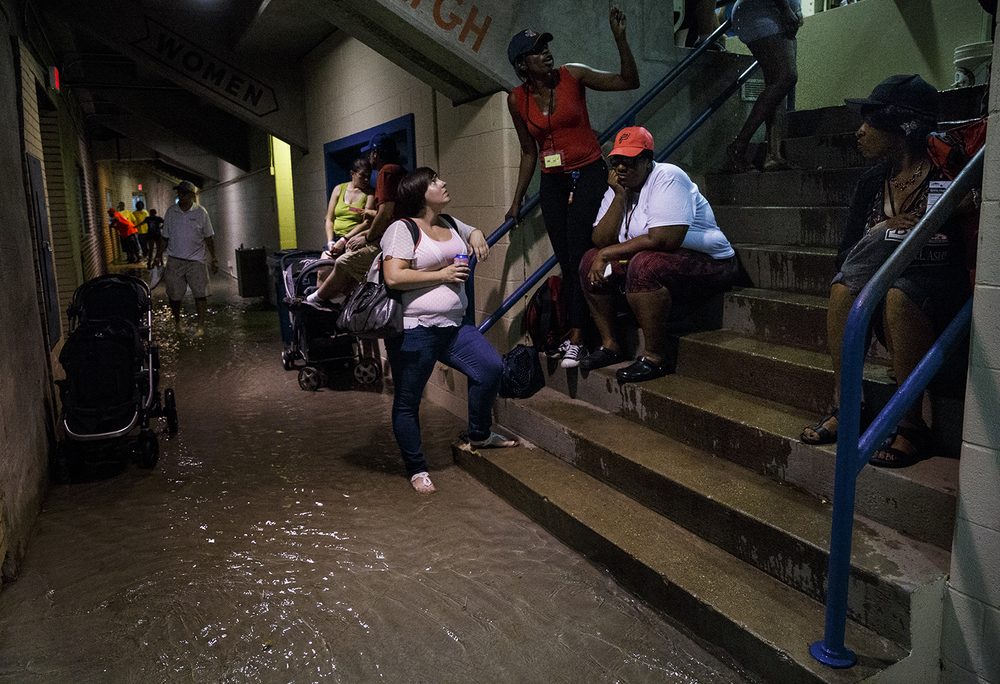 Fairgoers wait out the torrential rains inside the flooded Coliseum on the Illinois State Fairgrounds Friday, Aug. 12, 2016. Ted Schurter/The State Journal-Register