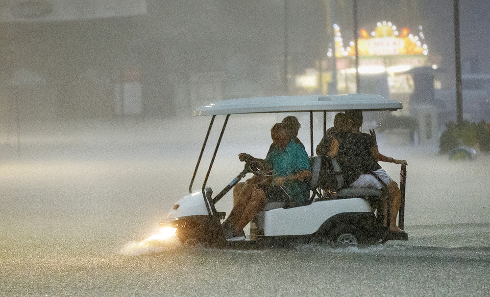 A golf cart navigates the flooded streets of the Illinois State Fairgrounds after picking up stranded passengers at the Colliseum during a torential downpour Friday, Aug. 12, 2016.  Ted Schurter/The State Journal-Register