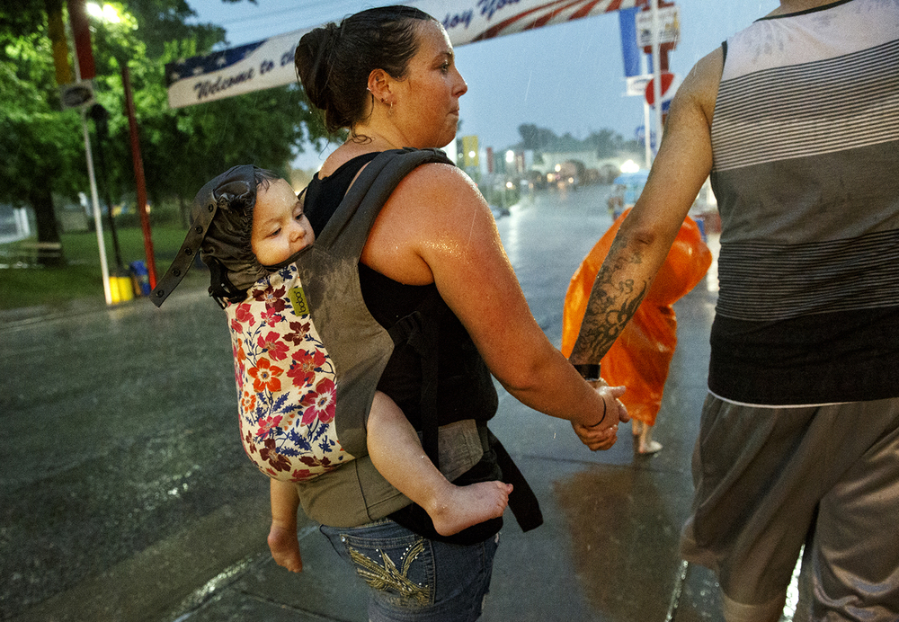 Christi Gaskin carries her daughter Alexia Belcher on her back as she makes her way back to the car with husband Bradley Belcher and her son Dayne during a downpour at the Illinois State Fairgrounds Friday, Aug. 12, 2016. The torrential rains flooded streets on the fairgrounds and surrounding areas. Ted Schurter/The State Journal-Register