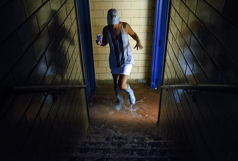 Tracy Madonia steps through the floodwaters pouring down to the bottom of the restroom stairs in the Coliseum during a torrential rainstorm Friday, Aug. 12, 2016. Ted Schurter/The State Journal-Register