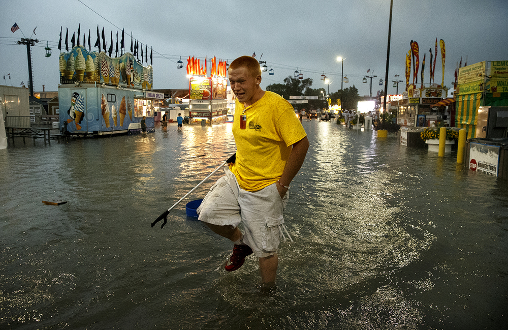 An Illinois State Fair employee makes his way down Central Avenue after torrential rains flooded the street Friday, Aug. 12, 2016. Ted Schurter/The State Journal-Register