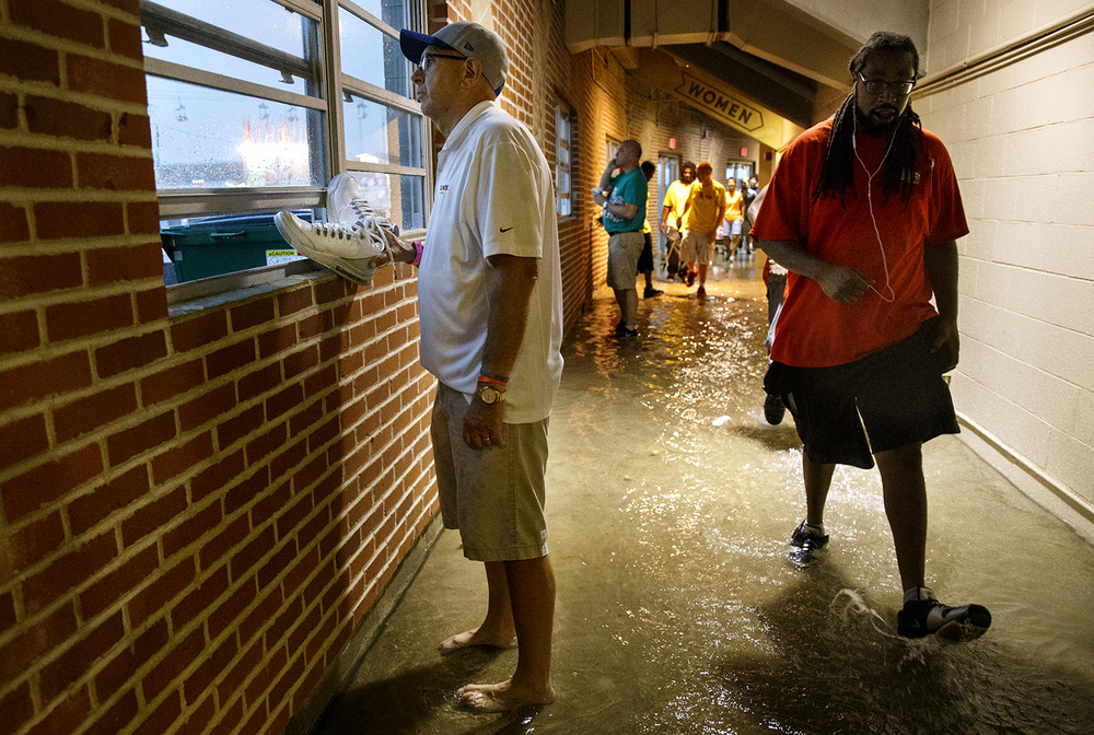 Dwight Garrels keeps his shoes dry as he stands barefoot in the flooded Coliseum at the Illinois State Fairgrounds Friday, Aug. 12, 2016. Ted Schurter/The State Journal-Register
